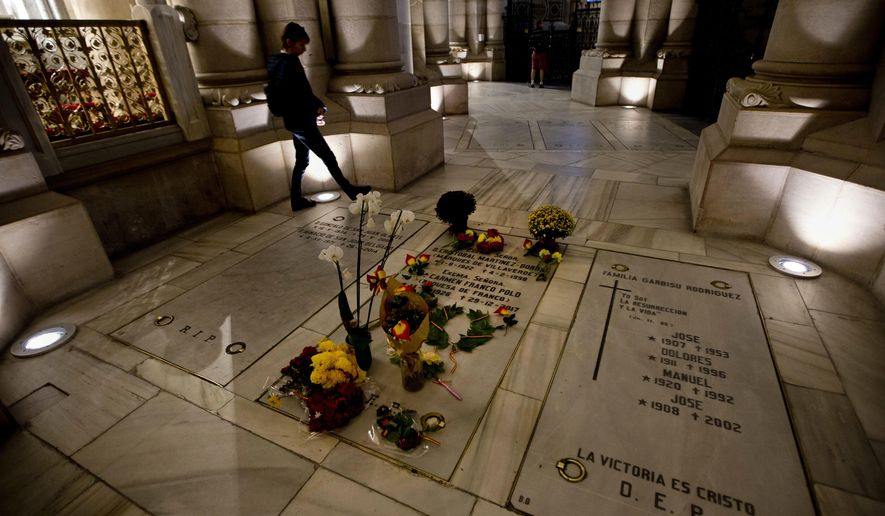 A person walks by the Franco family burial space adorned with flowers in the Almudena Crypt, a cavernous late-19th century Catholic temple under Madrid's Almudena cathedral, in central Madrid, Spain, Thursday Oct. 25, 2018.Hundreds of protesters in Madrid are urging government and Catholic church authorities to prevent the remains of the country's 20th century dictator from ending in the city's cathedral. Spain's center-left government has promised to exhume this year Gen. Francisco Franco from a glorifying mausoleum, but the late dictator's heirs have defied the plans by proposing for his remains to be relocated to a family crypt under the cathedral. (AP Photo/Paul White)