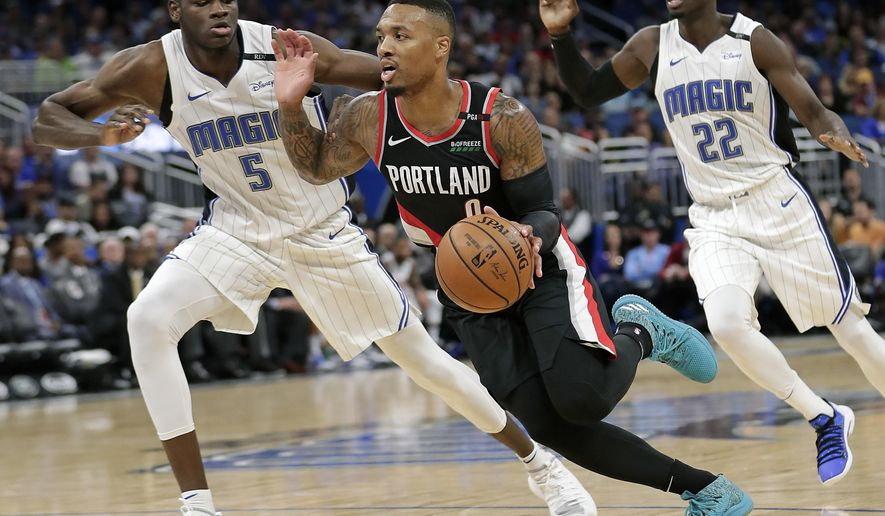 Portland Trail Blazers' Damian Lillard, center, drives to the basket between Orlando Magic's Jerian Grant (22) and Mohamed Bamba (5) during the second half of an NBA basketball game, Thursday, Oct. 25, 2018, in Orlando, Fla. (AP Photo/John Raoux)