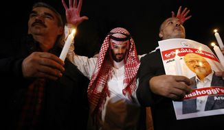 "An activist, wearing a mask depicting Saudi Crown Prince Mohammed bin Salman, holds up his hands, painted with fake blood as he protests the killing of Saudi journalist Jamal Khashoggi, during a candlelight vigil outside Saudi Arabia's consulate in Istanbul, Thursday, Oct. 25, 2018. The poster reads in Arabic:' Khashoggi's Friends Around the World'. A group of Arab and international public, political and media figures are establishing a global association called ""Khashoggi's Friends Around the World""; ""to achieve justice for the freedom martyr"".(AP Photo/Emrah Gurel)"