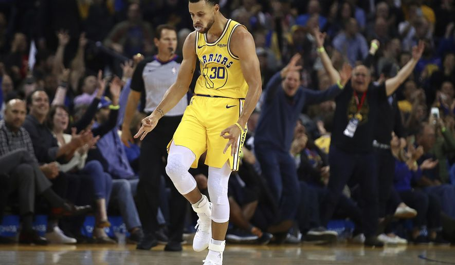 Golden State Warriors' Stephen Curry celebrates a score against the Washington Wizards during ...