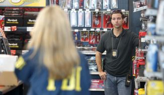 An FBI agent and a detective talk at an Auto Zone auto parts store, Friday, Oct. 26, 2018, in Plantation, Fla. Federal authorities took a man into custody Friday at the store in connection with the mail-bomb scare that earlier widened to 12 suspicious packages, the FBI and Justice Department said. (AP Photo/Wilfredo Lee)