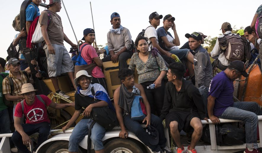 In this Oct. 24, 2018, file photo, Central American migrants traveling with a caravan to the U.S. crowd onto a tractor as they make their way to Mapastepec, Mexico. Militia groups and far-right activists are raising money and announcing plans to head to the Mexican border to help stop the caravan of Central Americans making their way toward the United States. (AP Photo/Rodrigo Abd) **FILE**