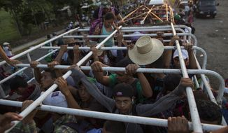 Migrants travel on a cattle truck, as a thousands-strong caravan of Central American migrants slowly makes its way toward the U.S. border, between Pijijiapan and Arriaga, Mexico, Friday, Oct. 26, 2018. Many migrants said they felt safer traveling and sleeping with several thousand strangers in unknown towns than hiring a smuggler or trying to make the trip alone. (AP Photo/Rodrigo Abd)