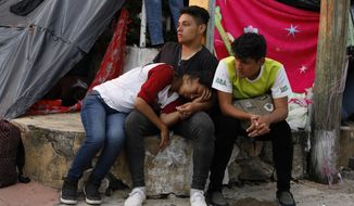Central American migrants rest as a thousands-strong caravan slowly making its way toward the U.S. border stops for the night in Pijijiapan, Chiapas state, Mexico, Thursday, Oct. 25, 2018. Little by little, sickness, fear, and police harassment are whittling down the migrant caravan making its way to the U.S. border, with many of the 4,000 to 5,000 migrants camped overnight in the southern town of Mapastepec complaining of exhaustion.(AP Photo/Rebecca Blackwell)