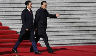 Japanese Prime Minister Shinzo Abe, left, walks with Chinese Premier Li Keqiang during a welcome ceremony at the Great Hall of the People in Beijing, Friday, Oct. 26, 2018.(AP Photo/Andy Wong)
