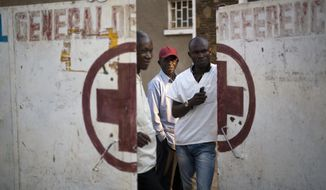 Employees guard the door of the Katuba Reference Hospital in Lubumbashi, Democratic Republic of the Congo on Monday, Aug. 13, 2018. An Associated Press investigation focused in Congo's second city, the copper-mining metropolis of Lubumbashi, discovered that of more than 20 hospitals and clinics visited, including this one, all but one detain patients unable to pay their bills. (AP Photo/Jerome Delay)