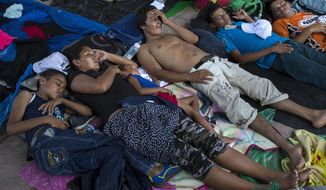 Honduran migrants rest in Pijijiapan, Mexico, Thursday, Oct. 25, 2018. Thousands of Central American migrants renewed their hoped-for march to the United States on Wednesday, setting out before dawn with plans to travel another 45 miles (75 kilometers) of the more than 1,000 miles that still lie before them. (AP Photo/Rodrigo Abd)
