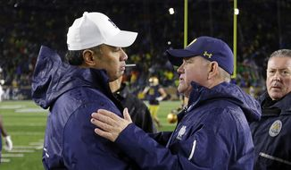 FILE - In this Nov. 18, 2017, file photo, Notre Dame head coach Brian Kelly, right, greets Navy head coach Ken Niumatalolo following an NCAA college football game in South Bend, Ind. No. 3 Notre Dame faces Navy on Saturday in San Diego.  (AP Photo/Michael Conroy, File) **FILE**