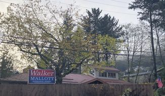 A Walker Mallott campaign sign is displayed outside the home of former Lt. Gov. Byron Mallott Friday, Oct. 26, 2018, in Juneau, Alaska. Gov. Bill Walker dropped his re-election campaign after Mallott resigned, and on Friday Walker asked supporters to take the campaign signs down. (AP Photo/Becky Bohrer)