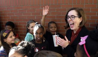 Oregon Gov. Kate Brown shares an unexpected light moment with a group of schoolchildren after a rally in Portland, Ore., Oct. 17, 2018. Brown, an incumbent and one of just two female Democratic governors nationwide, has struggled to create distance between herself and her GOP rival, a state lawmaker who has fashioned himself as a moderate Republican who appeals to independents and centrist Democrats alike with his anti-Trump and pro-choice platform. (AP Photo/Don Ryan)