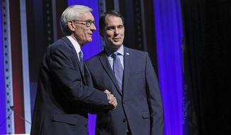 Republican Wisconsin Gov. Scott Walker, right, and Democratic challenger Tony Evers, left, meet onstage prior to the debate at the Zelazo Center on the University of Wisconsin-Milwaukee campus Friday, Oct. 26, 2018, in Milwaukee, Wis. (Michael Sears/Milwaukee Journal-Sentinel via AP)