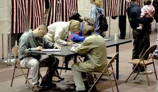 FILE - In this Tuesday, Nov. 2, 2004, file photo, a group of voters fill out their ballots at a table rather than wait for an empty voting booth at the Civic Center in Dodge City, Kan. After moving Dodge City, Kansas' sole polling site outside city limits, local election officials sent newly registered voters an official certificate of registration that lists the wrong place to cast a ballot in the midterm election. It is the latest election snafu to surface in this iconic Wild West town where Hispanics now make up the majority of the population. (Michael Schweitzer/Dodge City Daily Globe via AP, File)