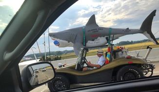 Delaware resident Art drives his shark-themed vehicle on the Del. 1 highway earlier this month. Wilson just likes being noticed while traveling with an attached 110-pound fiberglass shark atop his 1970 Volkswagen Beetle. (Andrew West Clayton /Delaware State News via AP)