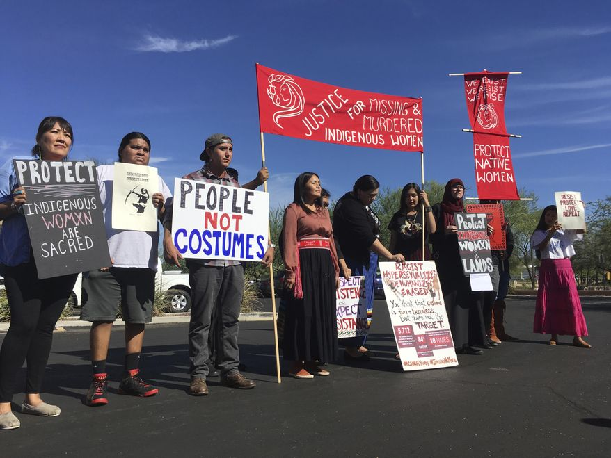 "Native American protesters stand outside the Phoenix office of Yandy.com, a retailer of ""sexy Native American"" costumes on Wednesday, Oct. 24, 2018. For some ethnic and racial groups, Halloween has long been haunted by costumes that perpetuate stereotypes and instances of cultural appropriation. (AP Photo/Terry Tang)"