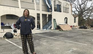 This Oct. 23, 2018 photo shows Regina Ferrell, a fourth grade teacher in Panama City, standing in front of her damaged condo building in Panama City, Fla. Since Hurricane Michael swept through the area, many teachers like Ferrell are sleeping in half-destroyed homes, living in cars or staying in their classrooms. (AP Photo/Tamara Lush)