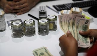 In this July 1, 2017, file photo, a person buys marijuana at the Essence cannabis dispensary in Las Vegas. (AP Photo/John Locher, File)