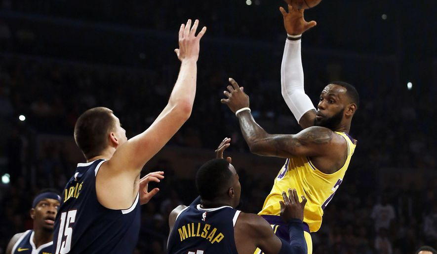 Los Angeles Lakers forward LeBron James, right, passes over Denver Nuggets center Nikola Jokic (15), of Serbia, and forward Paul Millsap (4) during the first half of an NBA basketball game in Los Angeles, Thursday, Oct. 25, 2018. (AP Photo/Alex Gallardo)