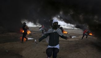Protesters run when burn tires near the fence of the Gaza Strip border with Israel during a protest east of east of Gaza City, Friday, Oct. 26, 2018. (AP Photo/Adel Hana)