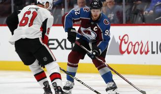 Colorado Avalanche left wing Gabriel Landeskog, right, looks to pass the puck past Ottawa Senators right wing Mark Stone in the first period of an NHL hockey game Friday, Oct. 26, 2018, in Denver. (AP Photo/David Zalubowski)