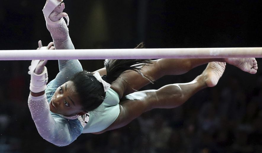 FILE - In this Aug. 19, 2018, file photo, Simone Biles competes on the uneven bars at the U.S. Gymnastics Championships, in Boston. Biles is focused on seeing how high she can soar. She is aware of the significant influence she wields in the sport still struggling from the fallout of the Larry Nassar sex abuse scandal. And she wants USA Gymnastics to take ownership of its issues and do what is right. She also wants her teammates competing at the world championships this weekend to be pushed in the right direction. (AP Photo/Elise Amendola, File)