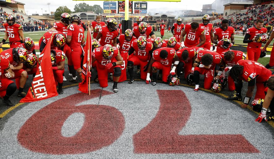 Maryland players gather at a No. 79 painted on the field in remembrance of offensive lineman Jordan McNair, who died after collapsing on a practice field during a spring practice, before an NCAA college football game against Illinois, Saturday, Oct. 27, 2018, in College Park, Md. (AP Photo/Patrick Semansky)