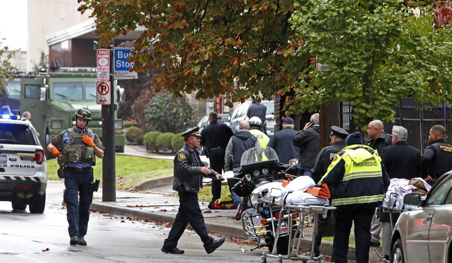 """First responders surround the Tree of Life synagogue, rear center, in Pittsburgh, where a shooter opened fire Saturday, Oct. 27, 2018, wounding three police officers and causing """"multiple casualties"""" according to Police. (AP Photo/Gene J. Puskar)"""