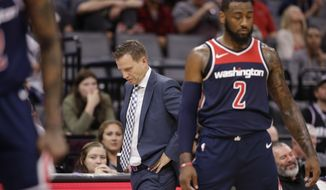 Washington Wizards head coach Scott Brooks, center, walks the sideline during the closing moments of the Wizards 116-112 loss to the Sacramento Kings in a NBA basketball game, Friday, Oct. 26, 2018, in Sacramento, Calif. At right is Wizards guard John Wall. (AP Photo/Rich Pedroncelli)