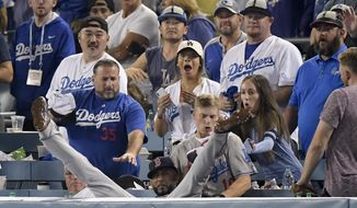 Boston Red Sox third baseman Eduardo Nunez falls into the stands after catching a foul ball hit by Los Angeles Dodgers' Cody Bellinger during the 13th inning in Game 3 of the World Series baseball game on Friday, Oct. 26, 2018, in Los Angeles. (AP Photo/Mark J. Terrill)