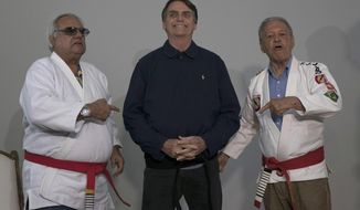 Brazilian presidential candidate Jair Bolsonaro smiles after receiving a honorary black belt from Jiu-Jitsu masters Robson Gracie, right, and Joao Carlos Austregesilo Athayde, in Rio de Janeiro, Brazil, Thursday, Oct. 25, 2018. Bolsonaro was awarded the honorary black belt out a respect for surviving a recent knife attack where he was wounded in the abdomen by a crazed attacker.  (AP Photo/Leo Correa)