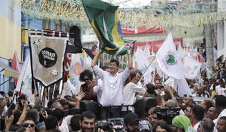 Fernando Haddad, Brazil's presidential candidate for the Workers' Party, holds a Brazilian flag during a campaign rally at the Heliopolis slum of Sao Paulo, Brazil, Saturday, Oct. 27, 2018. Haddad will face far-right congressman Jair Bolsonaro in a presidential runoff on Sunday. (AP Photo/Andre Penner)