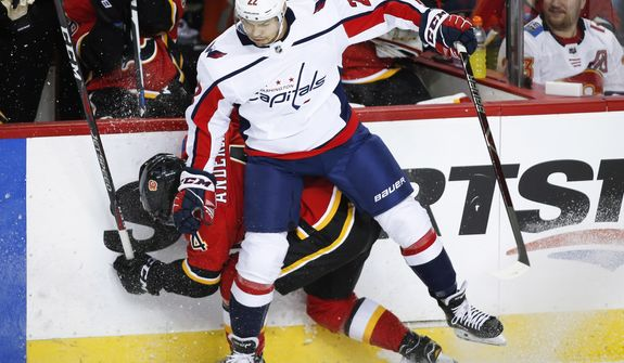Washington Capitals' Madison Bowey, right, checks Calgary Flames' Rasmus Andersson, of Sweden, during second period NHL hockey action in Calgary, Alberta, Saturday, Oct. 27, 2018. (Jeff McIntosh/The Canadian Press via AP) ** FILE **