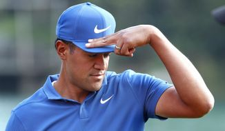 Tony Finau of the United States adjusts his cap during the second round of the HSBC Champions golf tournament held at the Sheshan International Golf Club in Shanghai, Friday, Oct. 26, 2018. (AP Photo/Ng Han Guan)