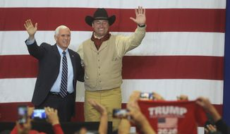 Vice President Mike Pence, left, and U.S. Senator Dean Heller wave to their supporters at the Carson City Airport on Saturday, Oct. 27, 2018, in Carson City, Nev. (JasonBean/The Reno Gazette-Journal via AP)