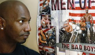 Former male dancer David Crosby, left, looks at a poster showing Cesar Sayoc, second from bottom and at right on motorcycle next to Crosby, Saturday, Oct. 27, 2018, in Hopkins, Minn. Sayoc was identified by authorities as the Florida man who allegedly sent pipe bombs to some of President Donald Trump's most prominent critics. Crosby said he worked with Sayoc about 12 years ago. (AP Photo/Jim Mone)