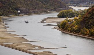 In this Oct.24, 2018 photo a cargo ship passes sandbanks near Kaub, Germany during historically low water on the river Rhine. A hot, dry summer has left German waterways at record low levels, causing chaos for the inland shipping industry, environmental damage and billions of euros of losses _ a scenario that experts warn could portend things to come as global temperatures rise. (AP Photo/Michael Probst)