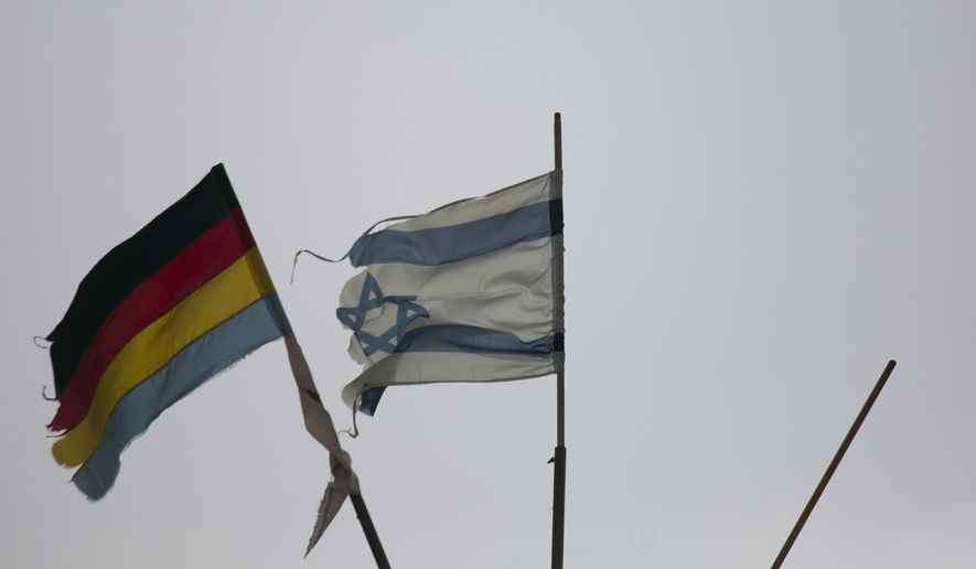 In this Oct. 17, 2018, photo, Israeli and Druze flags flutter on the village's council building in Ein Qiniya in the Israeli-controlled Golan Heights. (AP Photo/Ariel Schalit) **FILE**