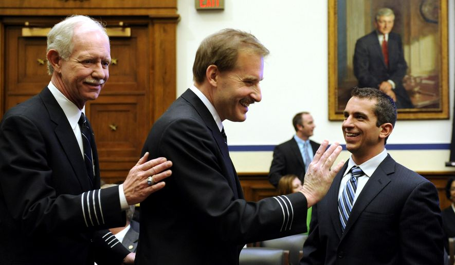 """FILE - In this Feb. 24, 2009, file photo, Air Traffic Control Specialist Patrick Harten, right, smiles as US Airways flight 1549 Capt. Chesley B Sullenberger III, right, and First Officer Jeffrey B. Skiles, center, arrive on Capitol Hill in Washington to testify before the House Transportation and Infrastructure Committee. The image is miraculous: Passengers standing on the wings of a US Airways jetliner as it floats down the Hudson River. Sullenberger and  Harten are forever linked because of the amazing outcome for all 155 passengers. Approaching the 10th anniversary of the """"Miracle on the Hudson,"""" they will meet at the finish line of the New York City Marathon. Sullenberger plans to put the finisher's medal around Harten's neck in Central Park on Nov. 4, 2018. (AP Photo/Susan Walsh)"""