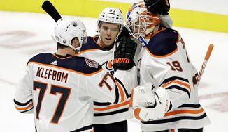 Edmonton Oilers goaltender Mikko Koskinen (19), of Finland, celebrates with defenseman Oscar Klefbom (77), of Sweden, and center Connor McDavid (97) after beating the Nashville Predators 5-3 in an NHL hockey game Saturday, Oct. 27, 2018, in Nashville, Tenn. (AP Photo/Mark Humphrey)