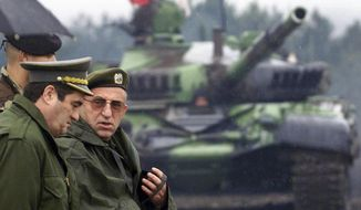 FILE - In this Sept. 1, 2000 file photo, former Yugoslav army chief of staff General Nebojsa Pavkovic, left, and General Vladimir Lazarevic, right, attend a military exercise, near the eastern Serbian town of Pirot, Serbia. A rights group has sharply criticized the Serbian government after the defense ministry published and promoted books written by Nebojsa Pavkovic and Vladimir Lazarevic, two former generals convicted of war crimes by a U.N. court. The Youth Initiative for Human Rights on Saturday, Oct. 27, 2018 said the move amounted to open state support for the war criminals.  (AP Photo/Darko Vojinovic, File)