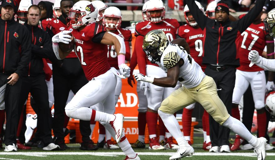 Louisville running back Trey Smith (12) breaks away from the pursuit of Wake Forest defensive back Essang Bassey (21) as he runs for a touchdown during the first half of an NCAA college football game, Saturday, Oct. 27, 2018, in Louisville, Ky. (AP Photo/Timothy D. Easley)