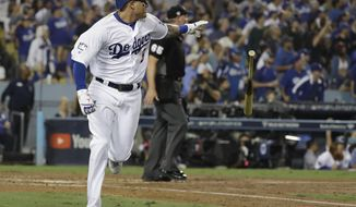 Los Angeles Dodgers' Manny Machado watches his single to deep left during the sixth inning in Game 3 of the World Series baseball game against the Boston Red Sox on Friday, Oct. 26, 2018, in Los Angeles. (AP Photo/David J. Phillip)