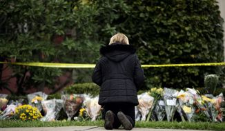 A mourner knelt before a makeshift memorial at the Tree of Life Synagogue in Pittsburgh on Sunday. (Associated Press)