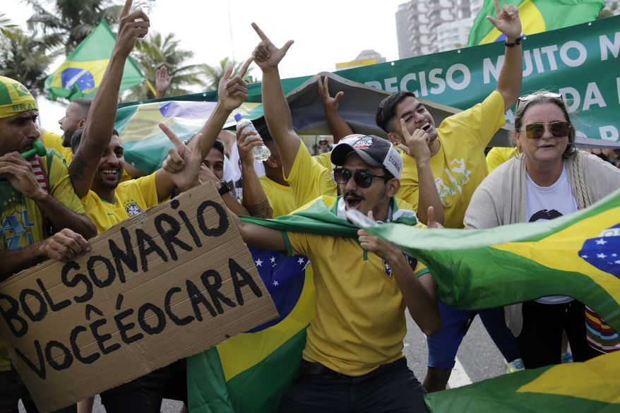 Supporters of Brazilian presidential candidate Jair Bolsonaro cheer as they gather outside his residence in Rio de Janeiro, Brazil, Sunday, Oct. 28, 2018, during the country's  presidential runoff election. Brazilians on Sunday were weighing their hunger for radical change against fears that Bolsonaro, the  presidential front-runner, could threaten democracy as they cast ballots in the culmination of a bitter campaign that split many families and was frequently marred by violence. (AP Photo/Leo Correa)