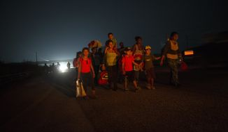 A family walks among other Central American migrants in a caravan of several thousand that is slowly making its way toward the U.S. border, outside Arriaga, Mexico, before dawn on Saturday, Oct. 27, 2018. Many migrants said they felt safer traveling and sleeping with thousands of strangers in unknown towns than hiring a smuggler or trying to make the trip alone. (AP Photo/Rodrigo Abd)