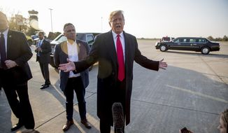 President Donald Trump, accompanied by Rep. Mike Bost, R-Ill., center left, speaks to reporters about a shooting at a Pittsburgh synagogue as he arrives at Southern Illinois Airport in Murphysboro, Ill., Saturday, Oct. 27, 2018, for a rally. (AP Photo/Andrew Harnik)