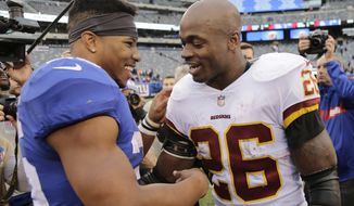 Washington Redskins Adrian Peterson, right, talks with New York Giants Saquon Barkley after an NFL football game, Sunday, Oct. 28, 2018, in East Rutherford, N.J. (AP Photo/Seth Wenig)