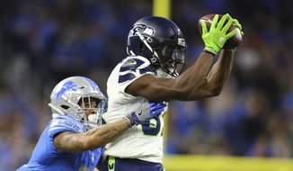 Seattle Seahawks wide receiver David Moore (83) makes a catch as Detroit Lions cornerback Teez Tabor defends during the first half of an NFL football game, Sunday, Oct. 28, 2018, in Detroit. (AP Photo/Rey Del Rio) ** FILE **