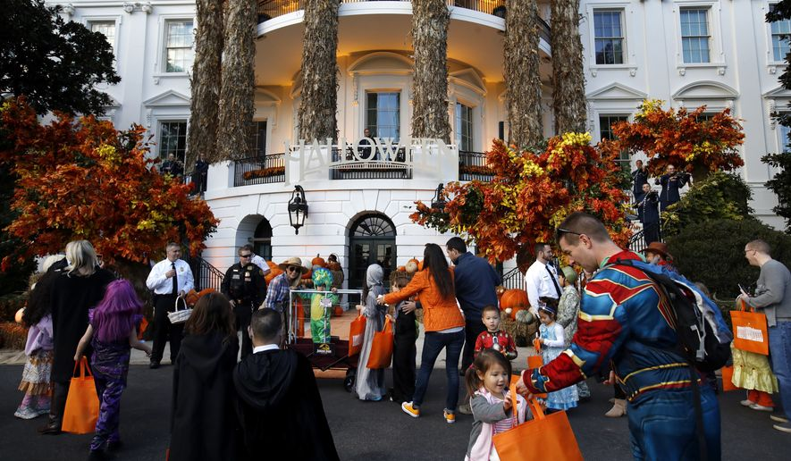 Families await the arrival of President Donald Trump and first lady Melania Trump at a Halloween trick-or-treat event at the White House, Sunday, Oct. 28, 2018, in Washington. (AP Photo/Jacquelyn Martin)