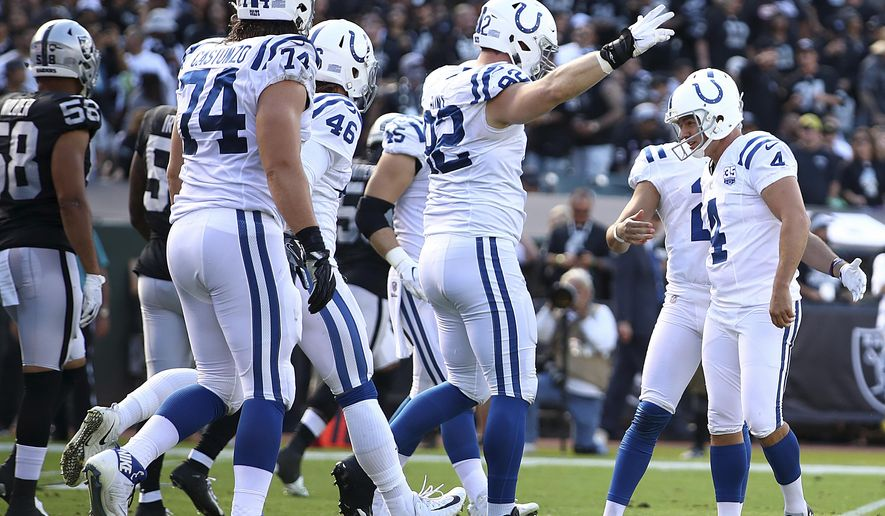 Indianapolis Colts kicker Adam Vinatieri, right, is congratulated by teammates after kicking a field goal against the Oakland Raiders during the first half of an NFL football game in Oakland, Calif., Sunday, Oct. 28, 2018. Vinatieri surpassed Morten Andersen's NFL record for points with this kick. (AP Photo/Ben Margot)