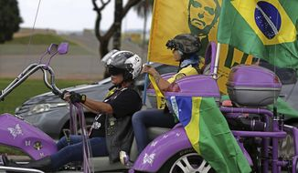 Mother and daughter carry flags on their tricycle during a rally in support of right-wing presidential candidate Jair Bolsonaro, in Brasilia, Brazil, Saturday, Oct. 27, 2018. Brazil is preparing for general elections to be held Sunday, Oct. 28. (AP Photo/Eraldo Peres)